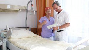Arzt und Hebamme besprechen Unterlagen